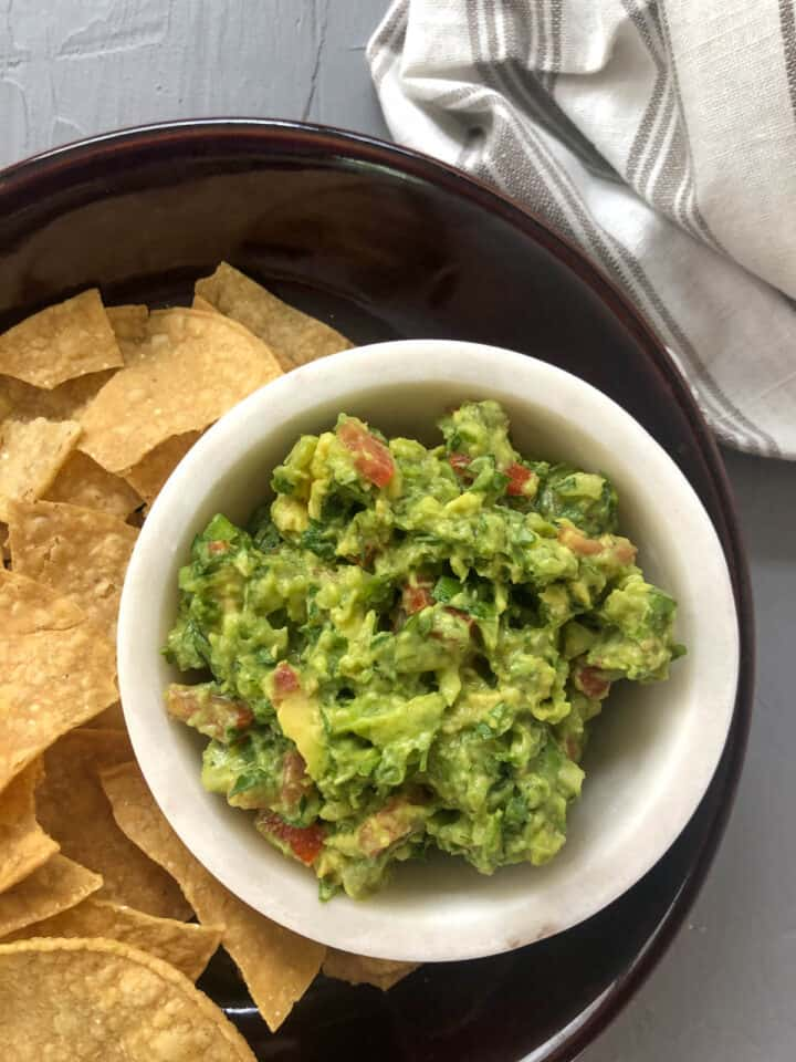 guacamole on a plate with chips