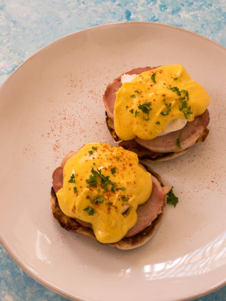 Eggs Benedict on a plate with hollandaise