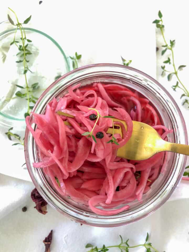 pickled red onion with a gold fork