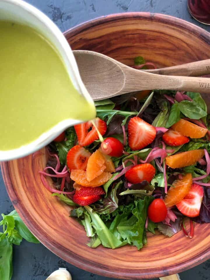 pouring white balsamic dressing on salad