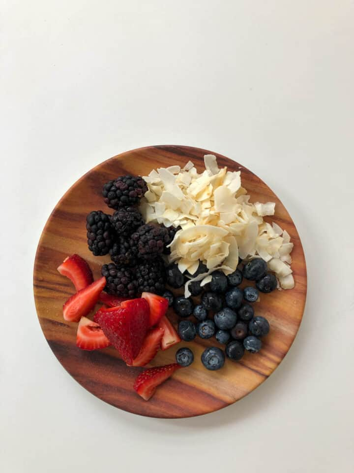 berries, and toasted coconut on a wooden plate