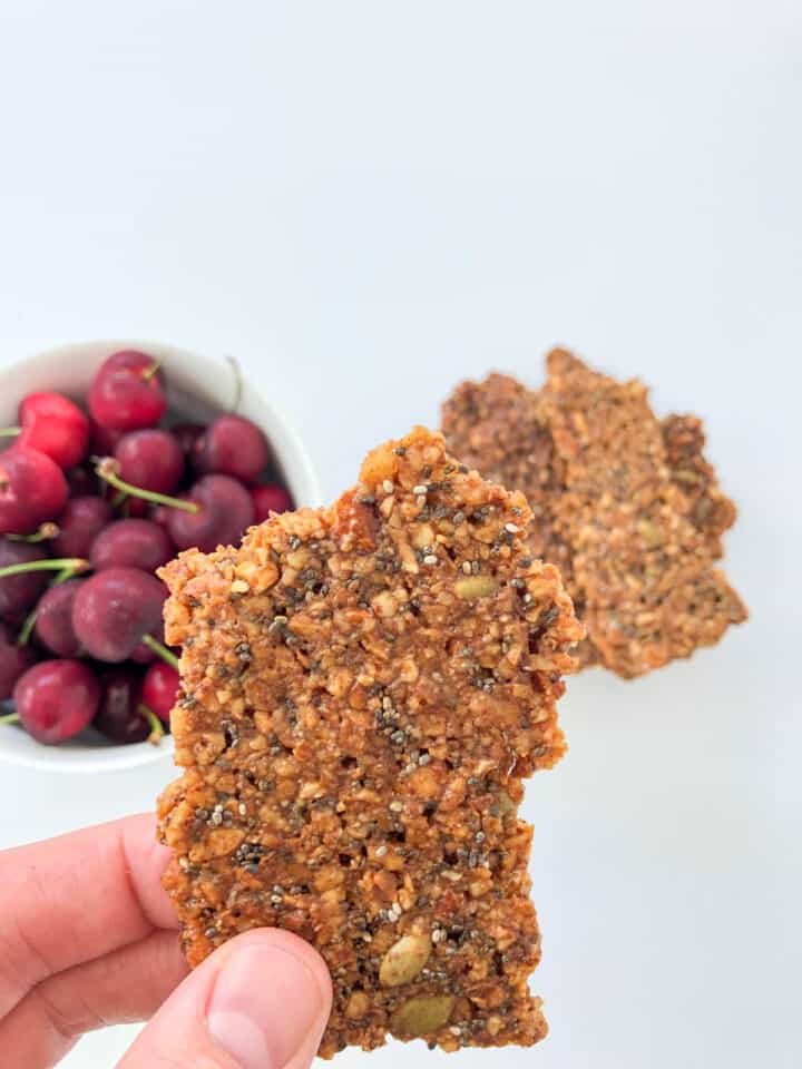 holding a chunk of granola with cherries