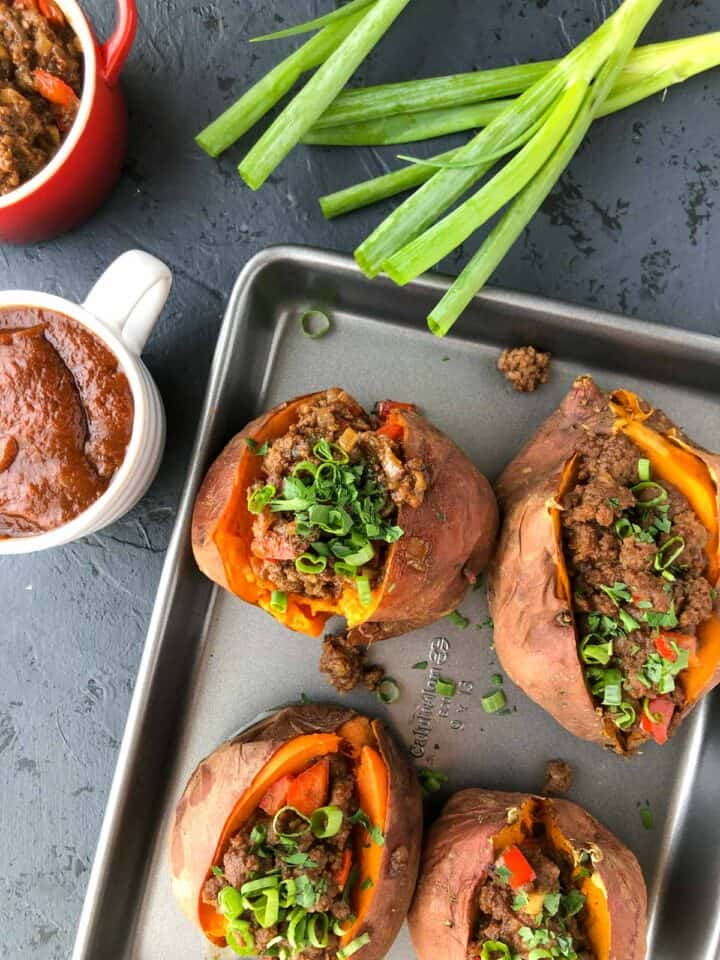 sloppy joes on baking tray with BBQ sauce and green onions