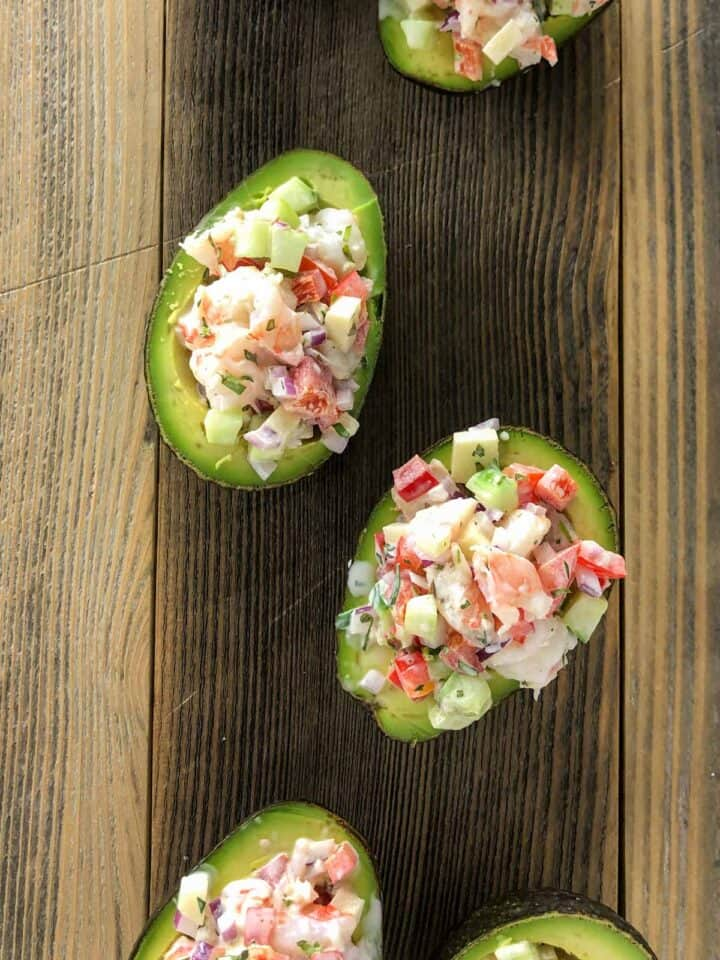 shrimp salad stuffed avocado on wooden board
