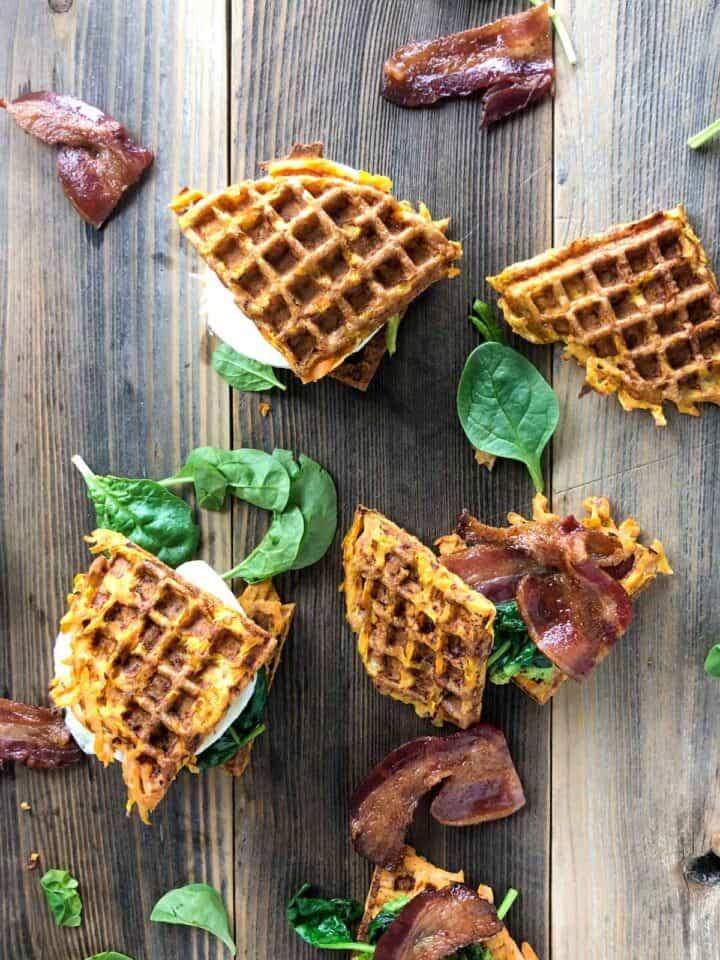 whole30 sweet potato waffle sandwich on a wooden board