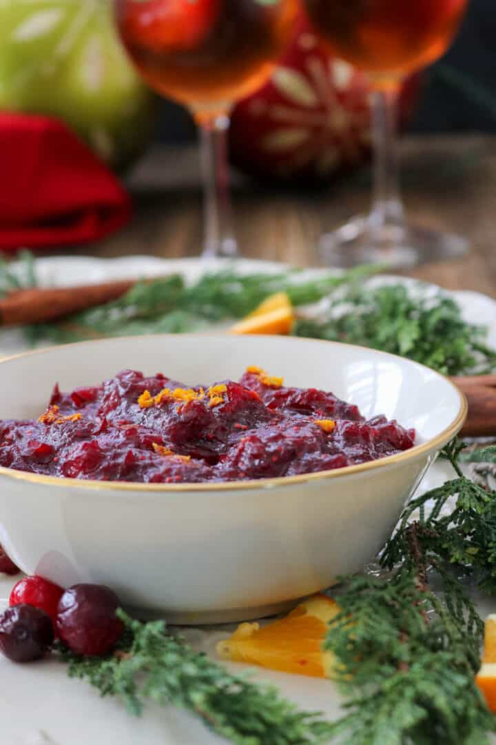 Quick homemade cranberry sauce on a platter with juniper leaves.